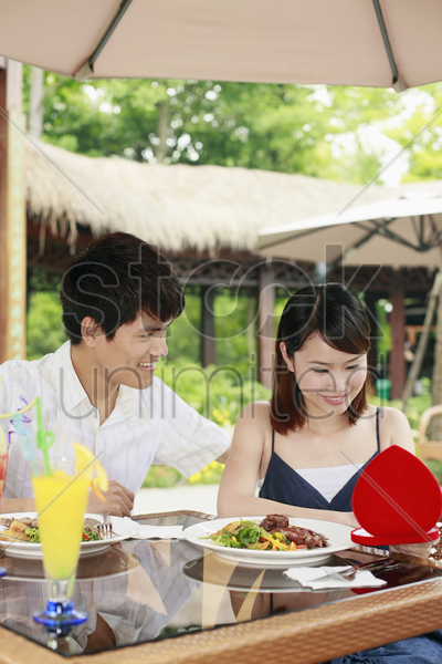 woman opening her present, man watching stock photo