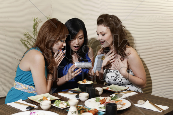 woman opening present, friends looking at the present in surprise stock photo