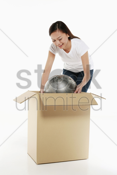 woman packing globe into a box stock photo
