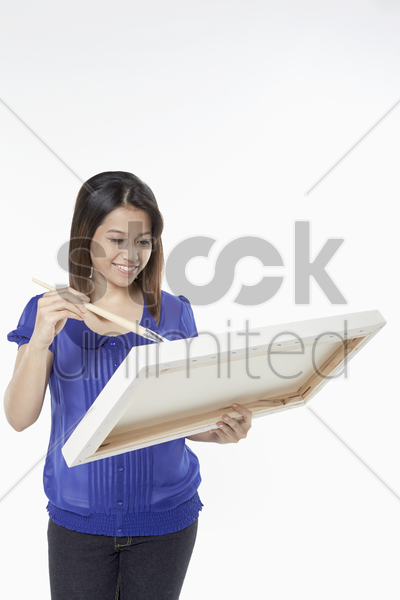 woman painting on a blank easel stock photo
