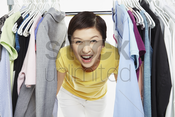 woman peering through a railing of clothes stock photo
