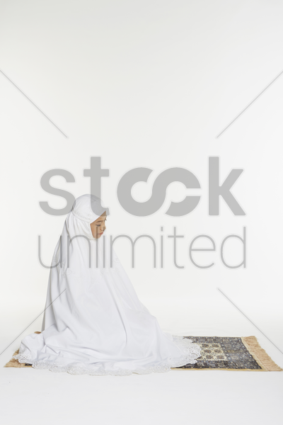 woman performing the sitting for tahiyyat stock photo