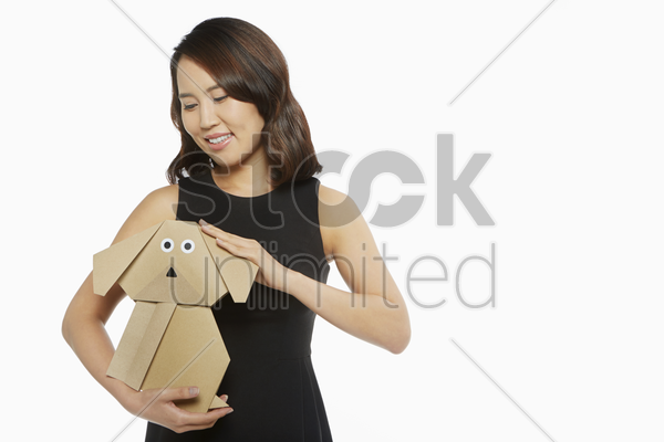 woman petting a dog made of cardboard stock photo