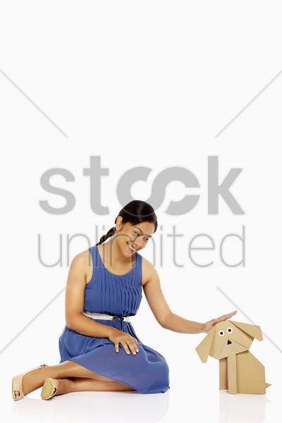 woman petting a paper dog stock photo