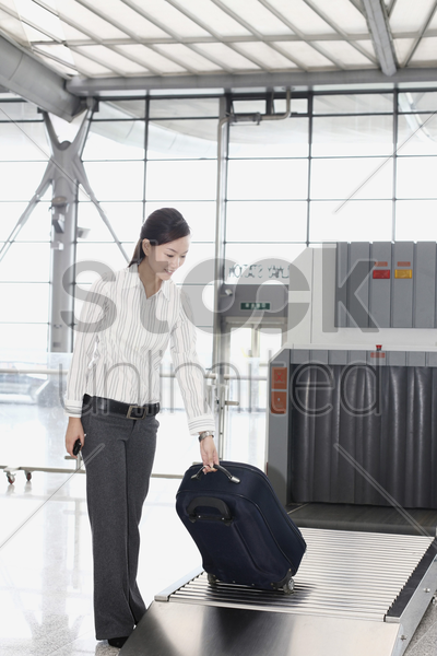 woman picking her luggage from the airport carousel stock photo