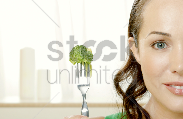 woman picking up broccoli with a fork stock photo