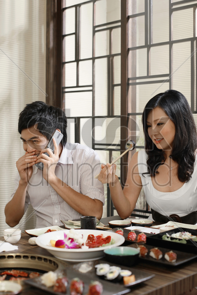 woman picking up sushi with chopsticks, man giggling while talking on the phone stock photo