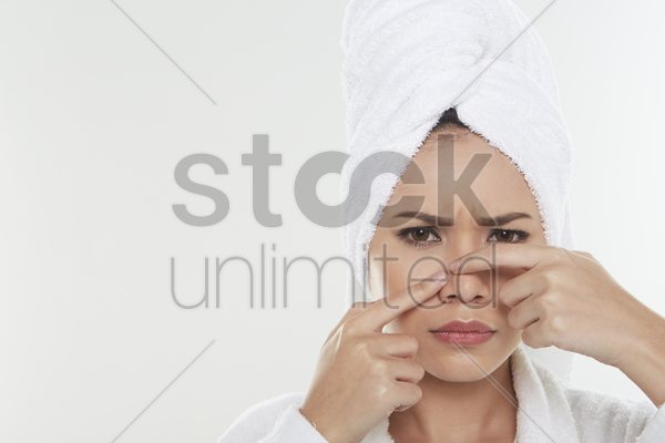 woman pinching pimple on her face stock photo