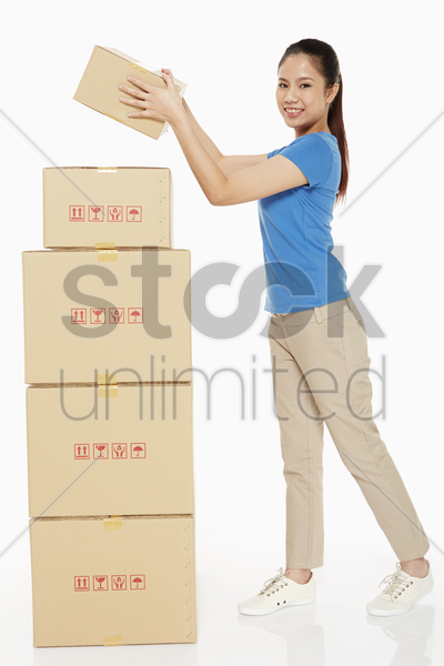 woman placing a cardboard box on stack of boxes stock photo