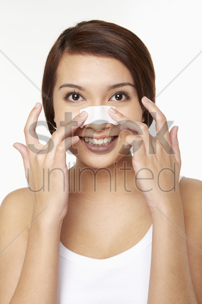woman placing cleansing strip on nose stock photo