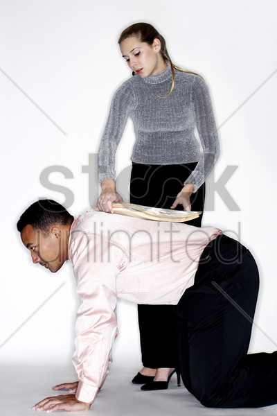 woman placing documents on her colleague's back stock photo
