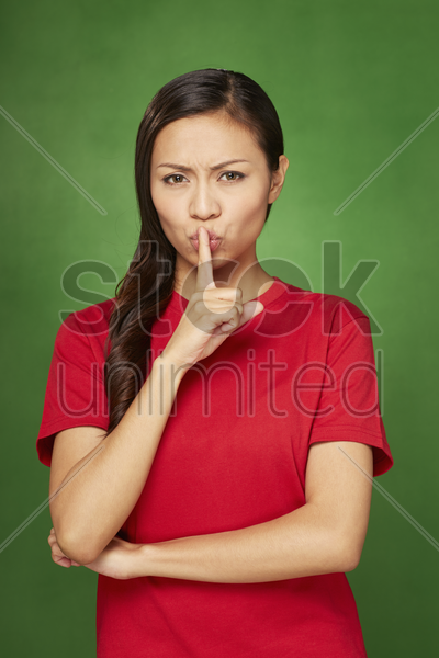 woman placing finger on her lips stock photo