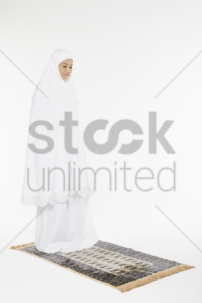 woman placing right hand on top of left hand against her chest stock photo