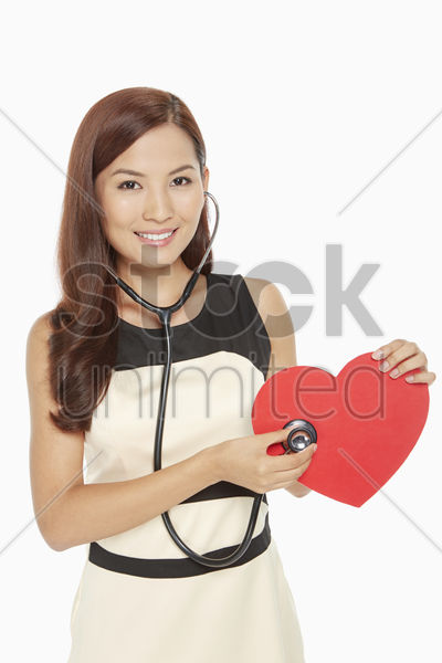 woman placing stethoscope on a cut out heart stock photo
