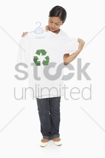 woman placing t-shirt against her body stock photo