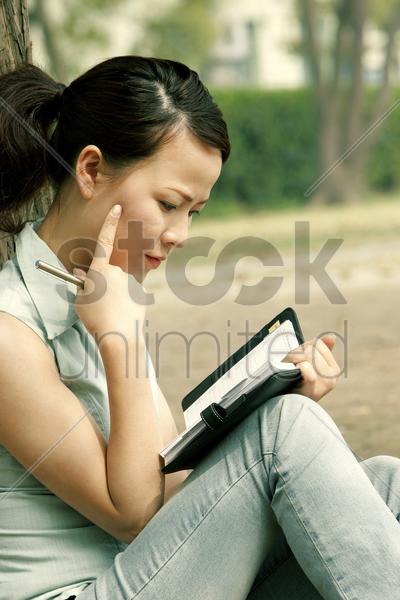 woman planning her schedule on her organizer stock photo