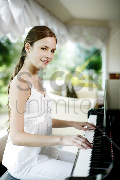 woman playing piano at home stock photo