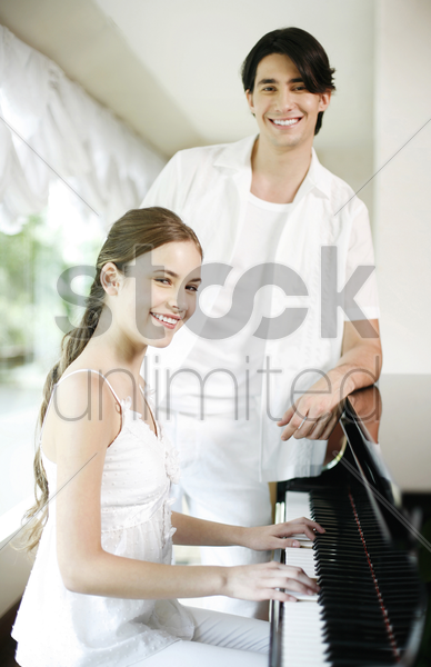 woman playing piano with her boyfriend standing beside her stock photo