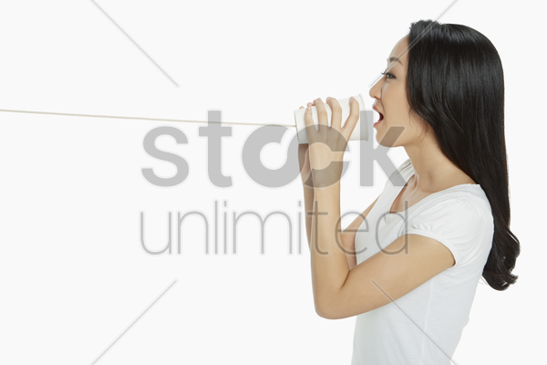 woman playing with a paper cup phone stock photo