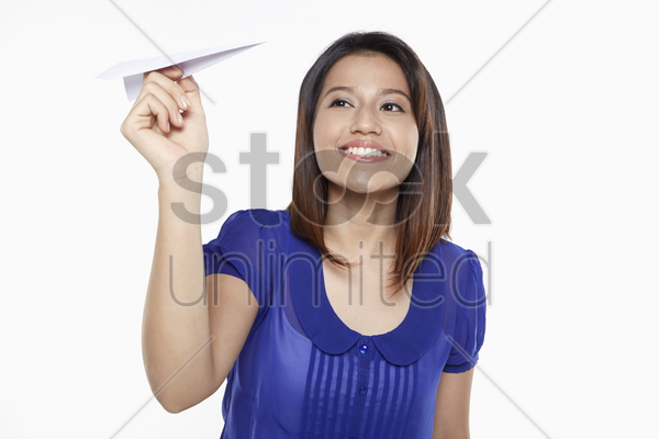 woman playing with paper airplane stock photo