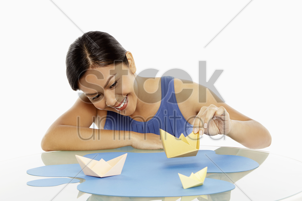 woman playing with paper boats stock photo