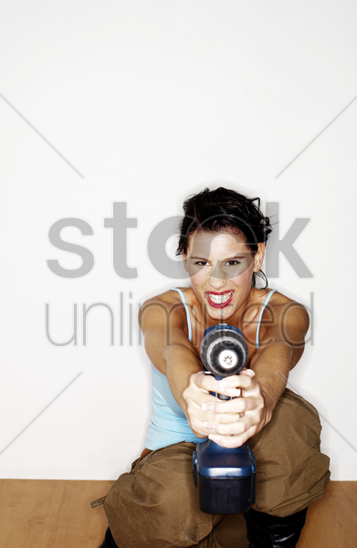woman pointing a drill at the camera stock photo