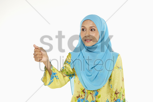woman pointing using her thumb stock photo