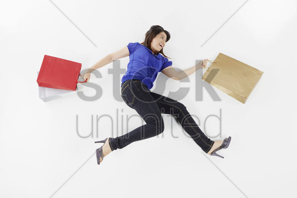 woman posing on the floor with shopping bags stock photo