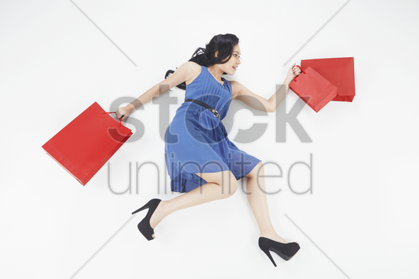 woman posing on the ground while carrying shopping bags stock photo