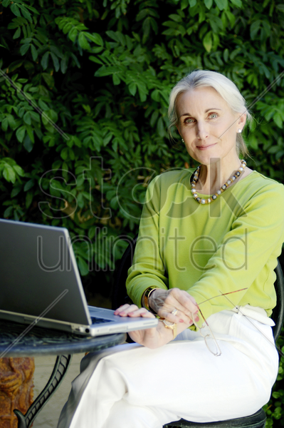 woman posing with a laptop on the table stock photo