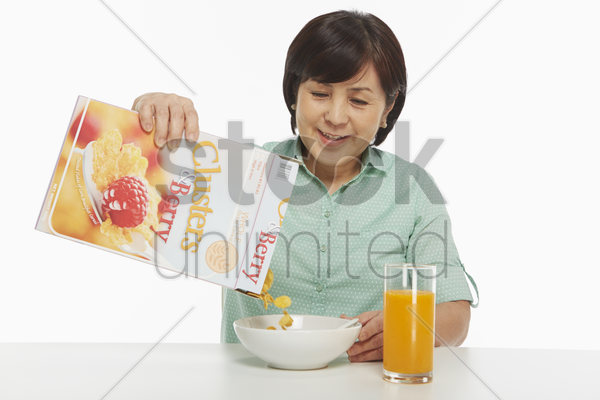 woman pouring cereals into bowl stock photo