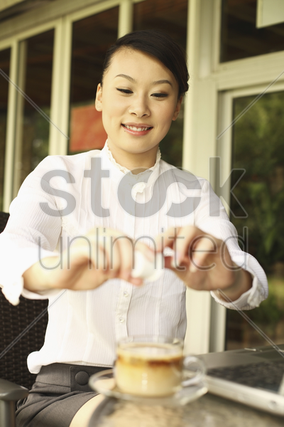 woman pouring creamer into her coffee stock photo