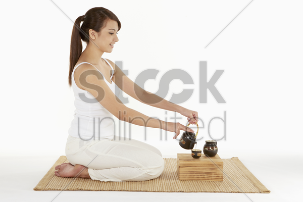 woman pouring tea into a cup stock photo