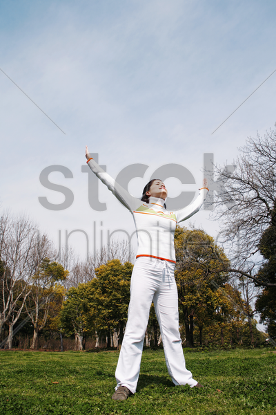 woman practicing yoga in the park stock photo