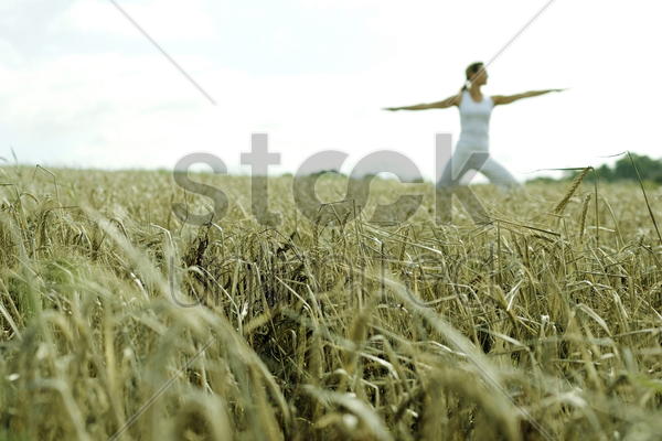 woman practicing yoga on the field stock photo