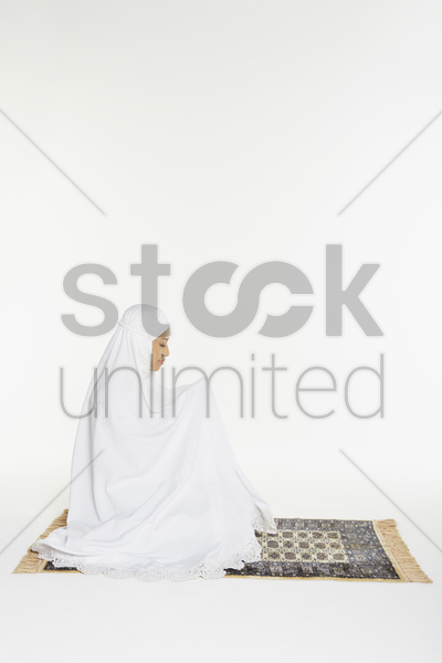 woman praying during the end recital of the prayer stock photo