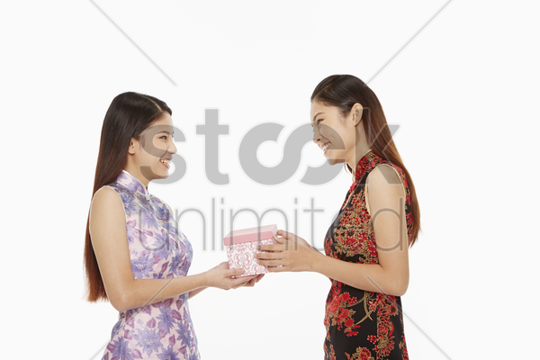 woman presenting gift to a friend stock photo