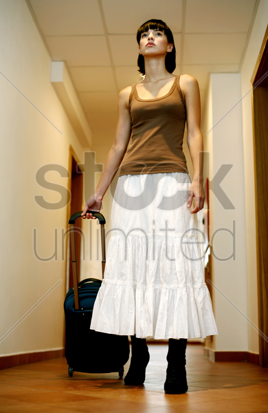 woman pulling a traveling bag stock photo