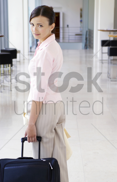 woman pulling her travelling bag stock photo