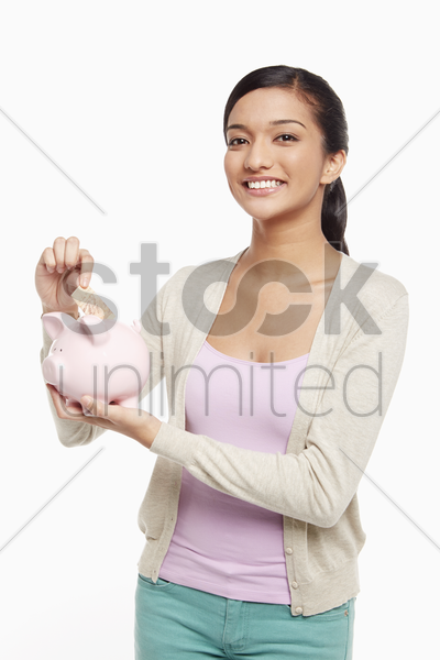 woman putting money into the piggy bank stock photo