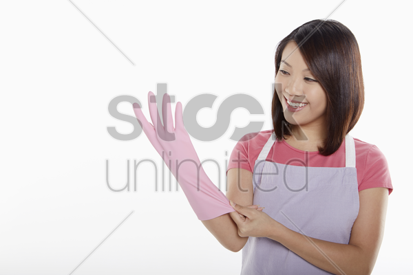 woman putting on rubber gloves stock photo