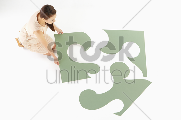 woman putting together a puzzle stock photo