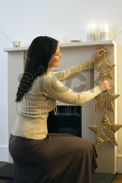 woman putting up a christmas ornament stock photo
