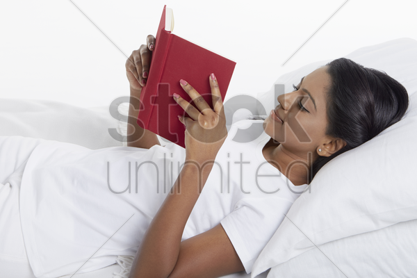 woman reading a book while lying on the bed stock photo