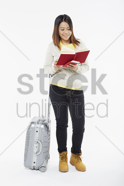 woman reading a book while standing stock photo