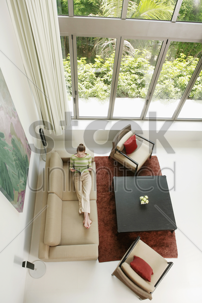 woman reading a magazine in the living room stock photo