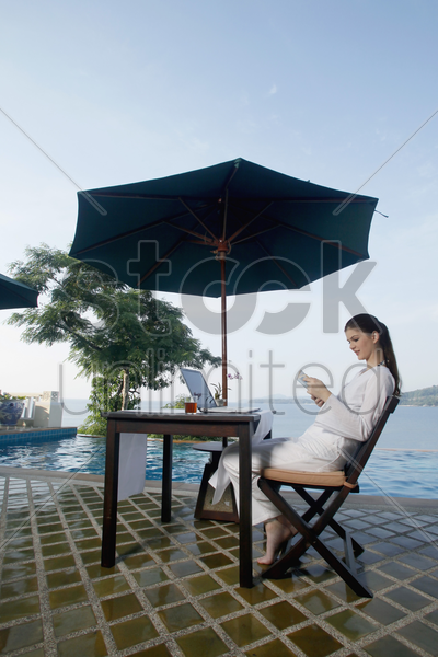 woman reading book by the pool side stock photo