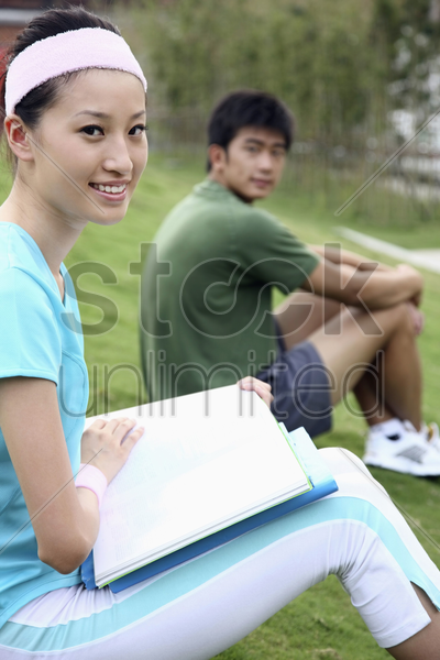 woman reading book, man sitting in the background stock photo