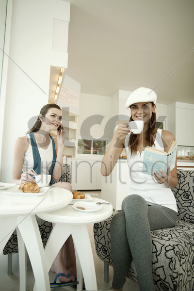 woman reading book while having coffee, another woman is on the phone stock photo