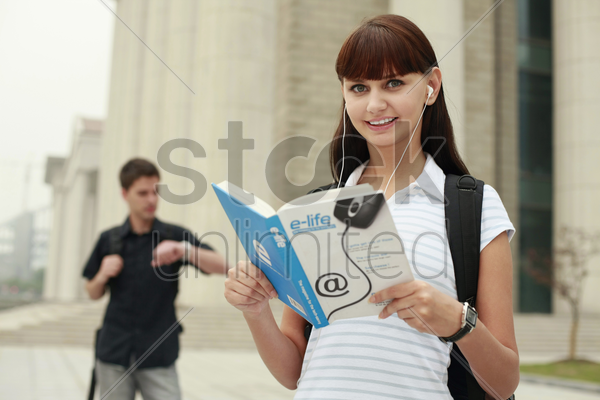 woman reading book while listening to music on portable mp3 player stock photo